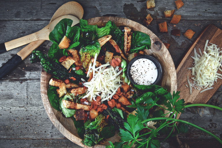 A Caesar salad made with crispy kale, grilled romaine lettuce, Quorn Pieces, and Quorn Vegetarian Bacon, topped with Parmesan and croutons with a dressing on the side.