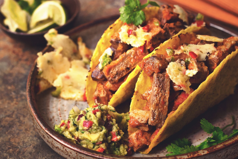 Two hard shell tacos filled with Quorn Vegetarian Steak Strips and queso fundido garnished with coriander and served on a black plate with guacamole on the side.