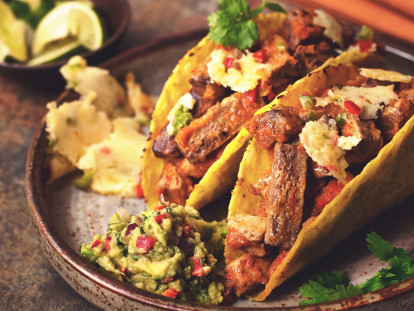 Two hard shell tacos filled with Quorn Meatless Steak-style Strips, cheese, and salsa, with guacamole and queso fundido on the side.