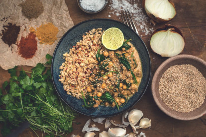 A chickpea and spinach curry made with Quorn Grounds topped with sesame seeds and served with a side of cooked oats and a wedge of lime.