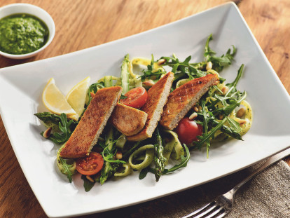 A sliced Quorn Fillet atop a bed of pasta with asparagus, arugula, and cherry tomatoes with two wedges of lemon and pesto on the side.