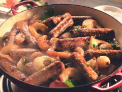 A casserole made with Quorn Sausages, shallots, and apples in a shallow Dutch oven.