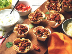 Vegetarian Quorn Mince Chilli filled in taco cups served on a wooden board with a side of cheese, yoghurt and cherry tomatoes