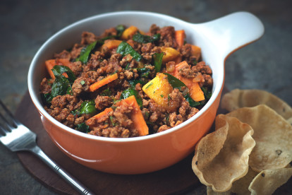 Spinach and sweet potato curry made with Quorn Grounds in an orange and white bowl with poppadums on the side.