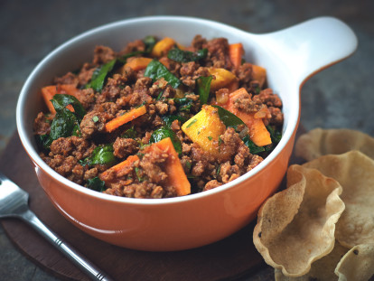 A casserole dish filled with Quorn Mince, Spinach and Sweet Potato Curry sat beside a serving of mini poppadums.