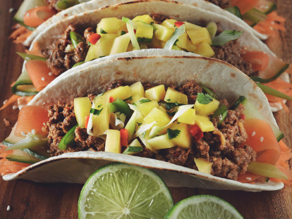 Two tacos in flour tortillas filled with ribbons of carrot and zucchini and Quorn Meatless Grounds, topped with mango salsa and served on a wooden plank with a wedge of lime on the side.