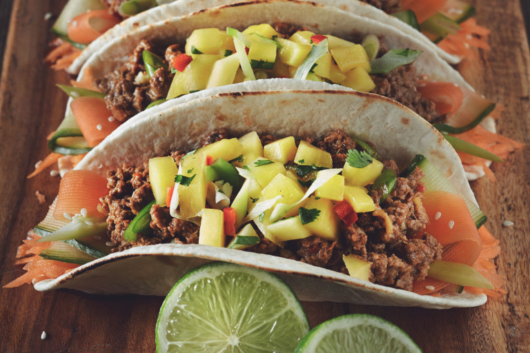 Three vegetarian Korean tacos made with flour tortillas filled with Quorn mince and pickled carrots and cucumbers and topped with mango salsa.