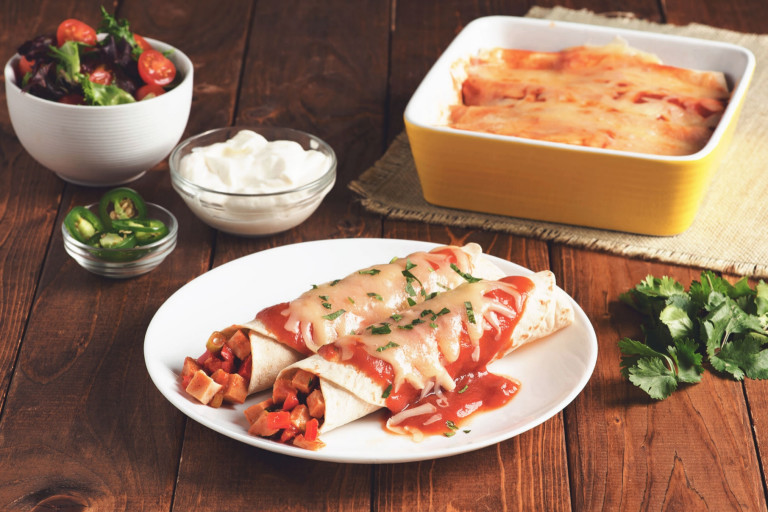 Two enchiladas made with flour tortillas topped with red sauce and cheese filled with Quorn Meatless Vegetarian Turkey Roast.