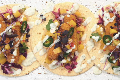 Tacos made with Quorn Vegan Fishless Fingers, jalapenos, diced mango and red cabbage served on tortillas drizzled with yoghurt