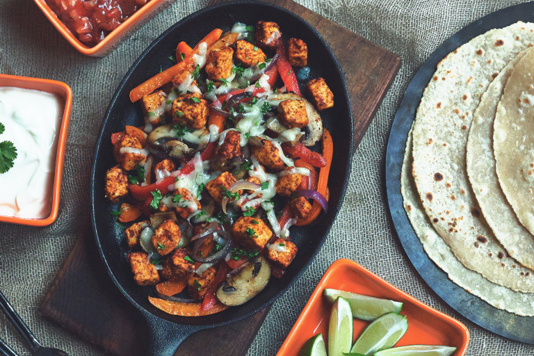 A hot skillet with a gluten free Quorn Fajitas sat beside corn tortillas and bowls of toppings.