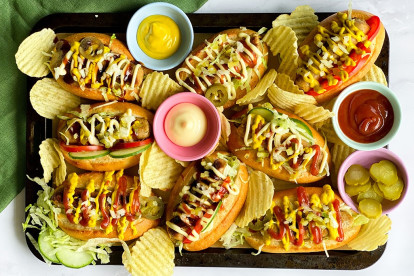 A platter of Chicago-style hot dogs made with Quorn sausages on bun topped with onion, dill pickles, tomatoes, cucumber, jalapenos, and lettuce with sauces and crisps on the side.