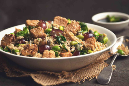 A quinoa salad with edamame, rice, halved grapes, kale, and Quorn Pieces in a white bowl.