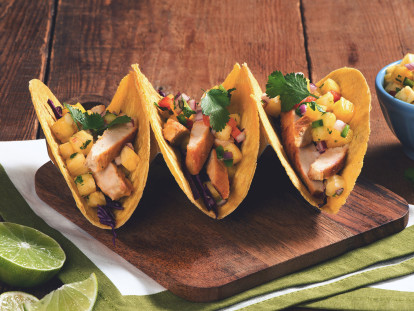 Three hard-shell corn tacos filled with Quorn Fillets, red cabbage, and pineapple salsa arranged on a wooden board with half of a lime and a blue ramekin of pineapple salsa on the side.