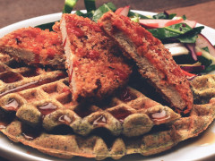 Quorn Meatless Vegan Chipotle Cutlets atop and blue corn waffle topped with syrup with collard green slaw on the side.