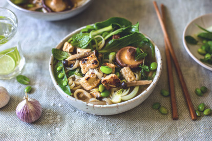 A bowl of rice noodle soup topped with mushrooms, peas, edamame, fresh herbs, bok choy, and Quorn Pieces, with a scattering of salt and edamame, a head of purple garlic, and chopsticks surrounding it.
