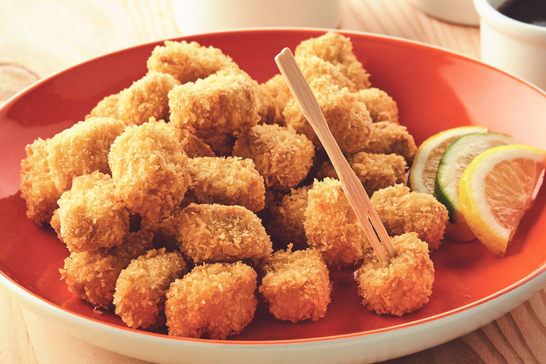 A plate piled high with breaded popcorn bites made with Quorn Pieces with citrus wedges on the side for serving.