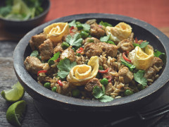 Rice dish of Nasi Goreng made with Quorn Pieces, served in a bowl topped with chilli, coriander and omelette rolls