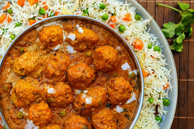 A shahi kofta masala curry made with Quorn Swedish Style Balls in a dish atop a bed of pulao rice.