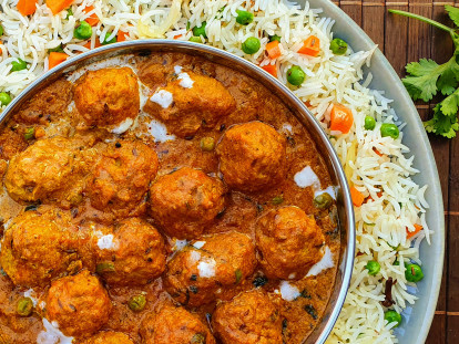 A shahi kofta masala curry made with Quorn Swedish Style Meatballs in a dish atop a bed of pulao rice.
