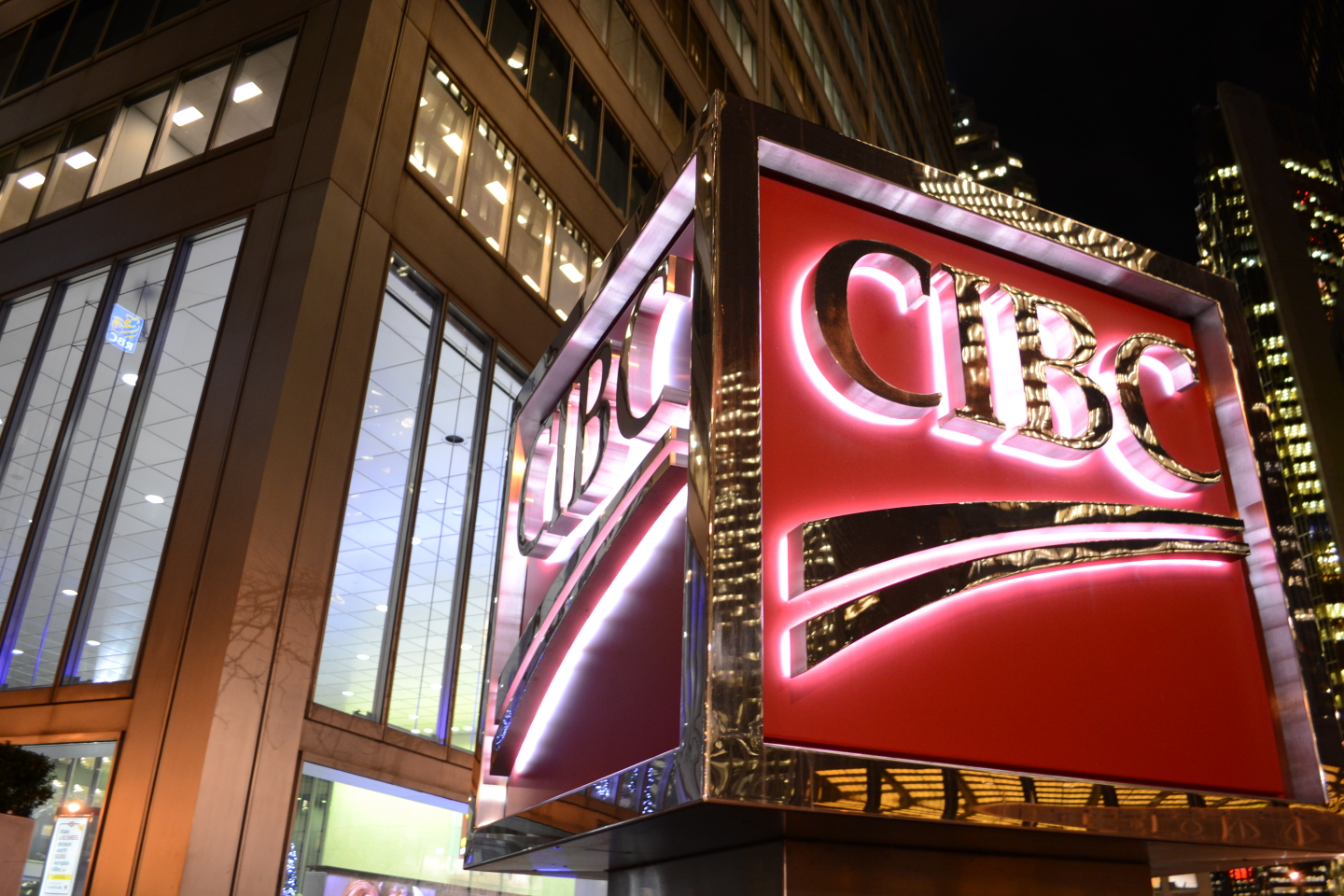 This photo is of the CIBC logo outside of the building. The CIBC logo is red and yellow and lit up in the dark.