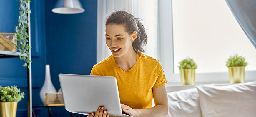 5 things improve your credit score - blog image - woman in yellow smiling at computer