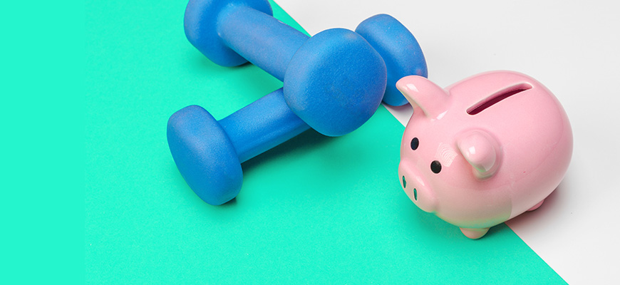 Weights and a piggy bank representing financial fitness