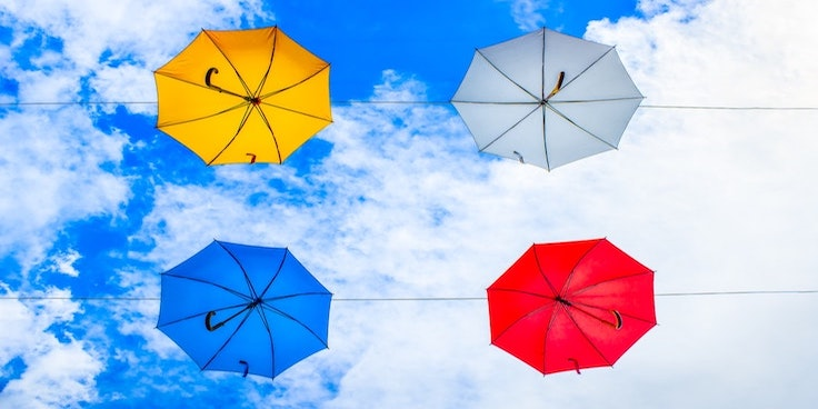 Different coloured umbrellas in the sky.