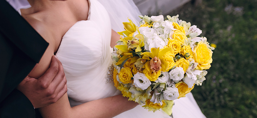 A photo of a couple about to be married. A beautiful yellow bouquet is held by the bride.