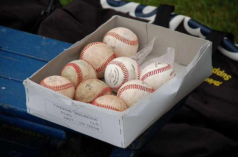 baseballs in a box on a bench