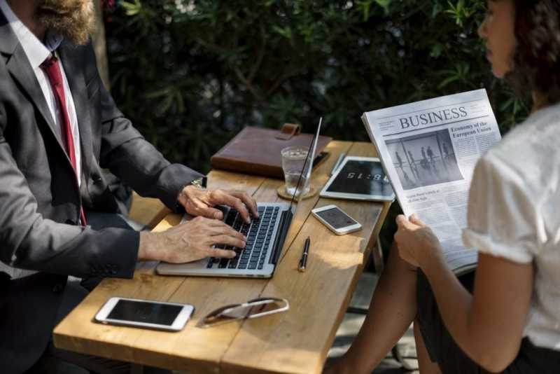 Photo of someone using a laptop and someone reading a newspaper