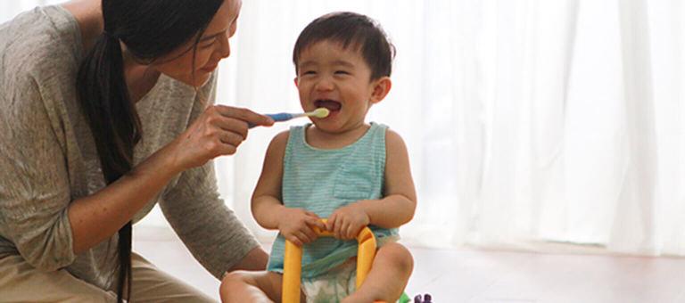 Bebeğinin dişini fırçalayan anne