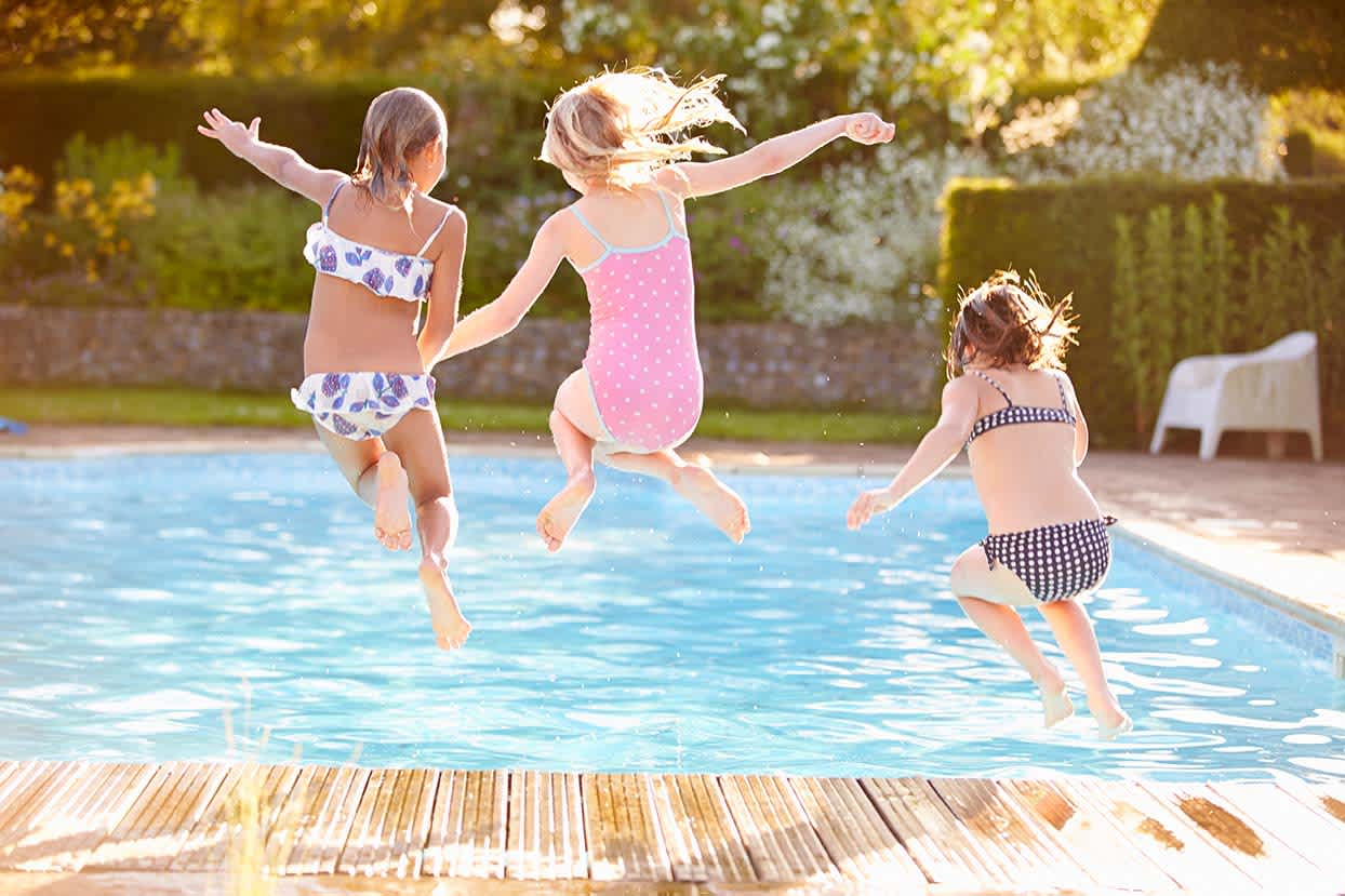 Kinder springen in den Swimmingpool