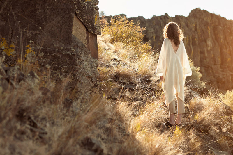 Woman in white poncho in desert