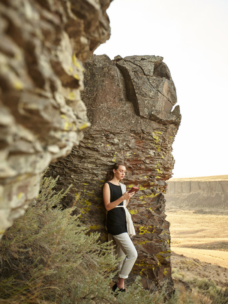 Woman leaning against a rock reading a book