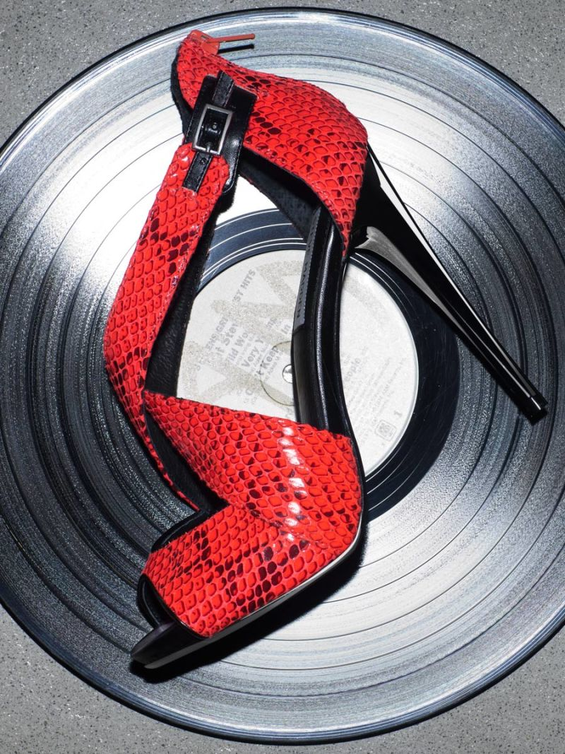 Red leather high heel on a record