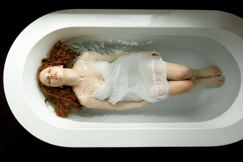 Woman in a dress in bath tub