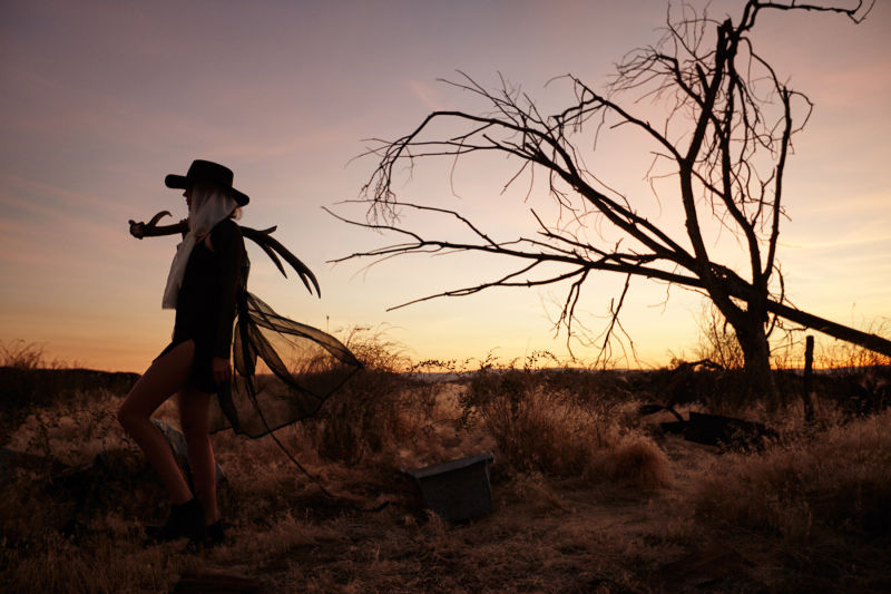 Woman carrying an antler at sunset