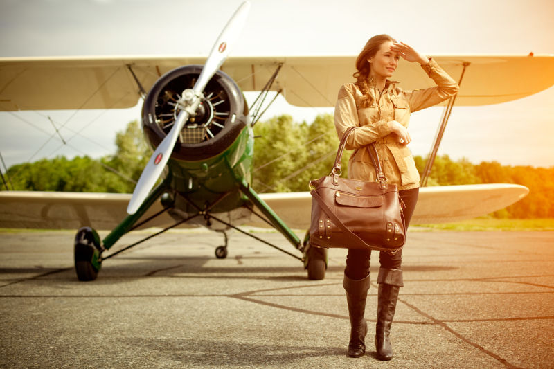 Woman shielding her eyes with purse near bi-plane