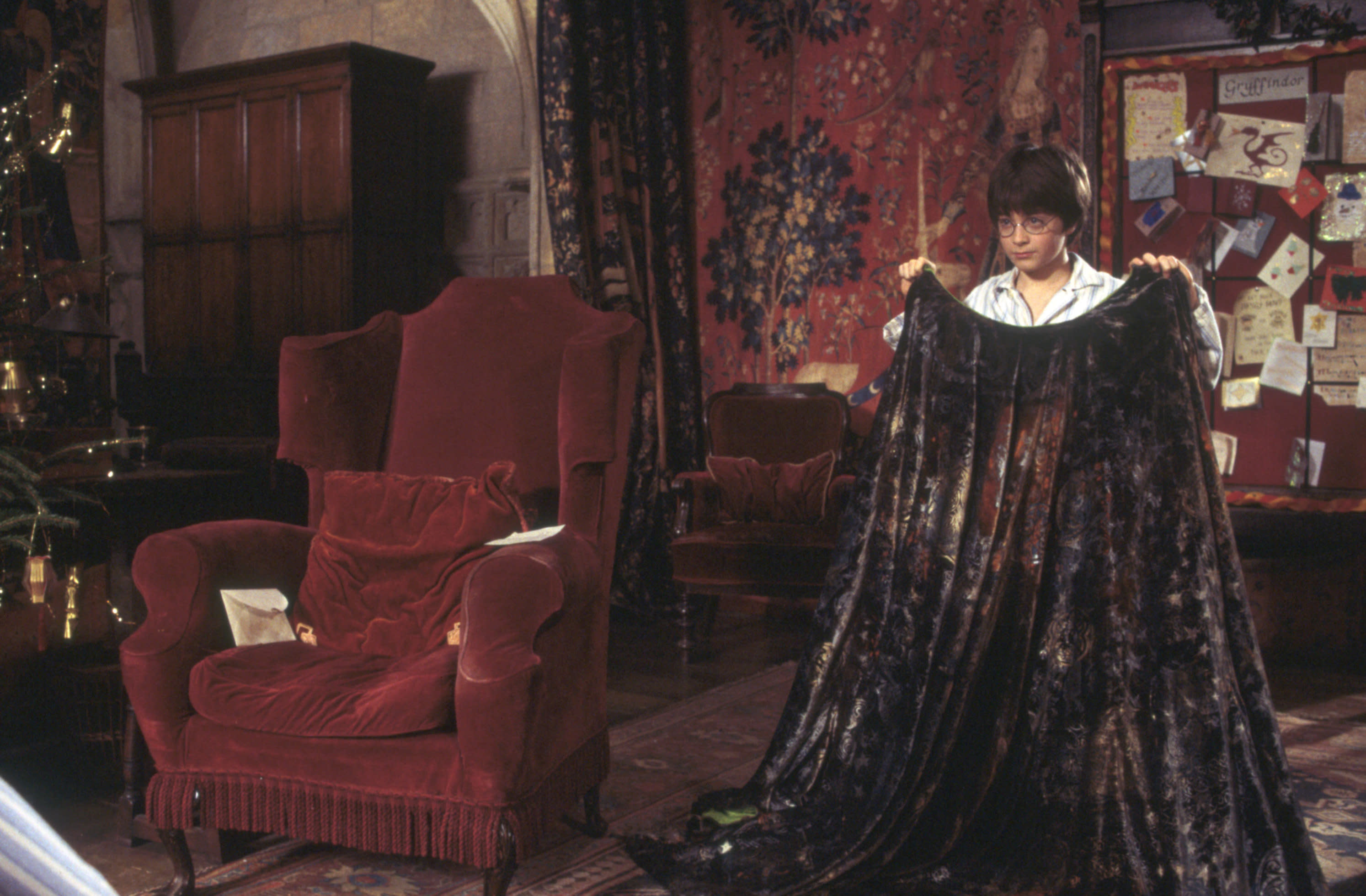 HarryPotter WB F1 HarryHoldingInvisibilityCloakInGryffindorCommonRoom Still 100615 Land