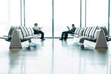 Two men sitting at the airport