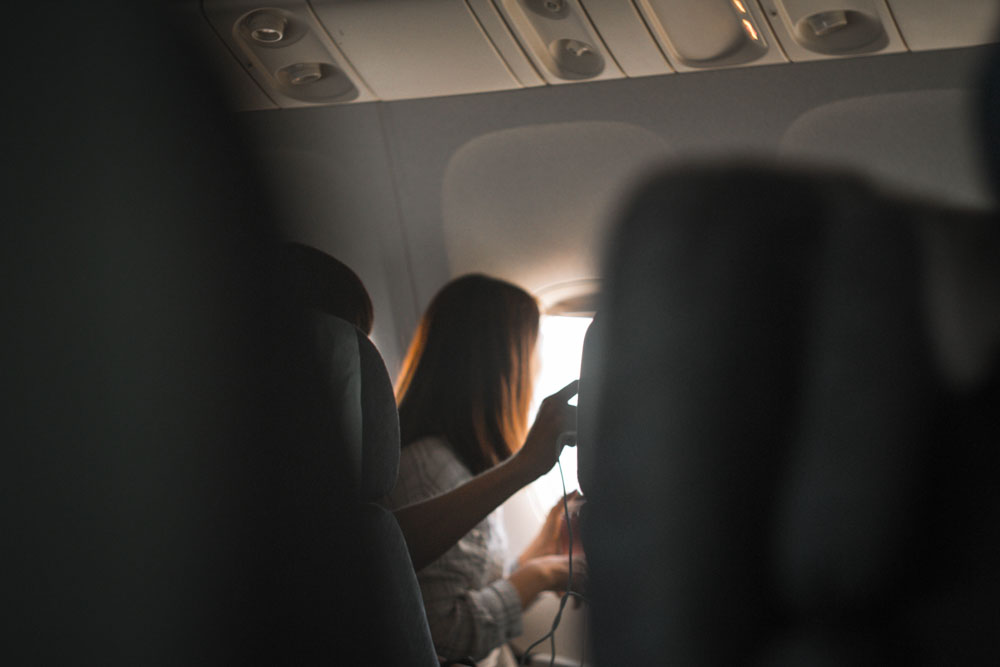 Woman sitting by the window of an airplane