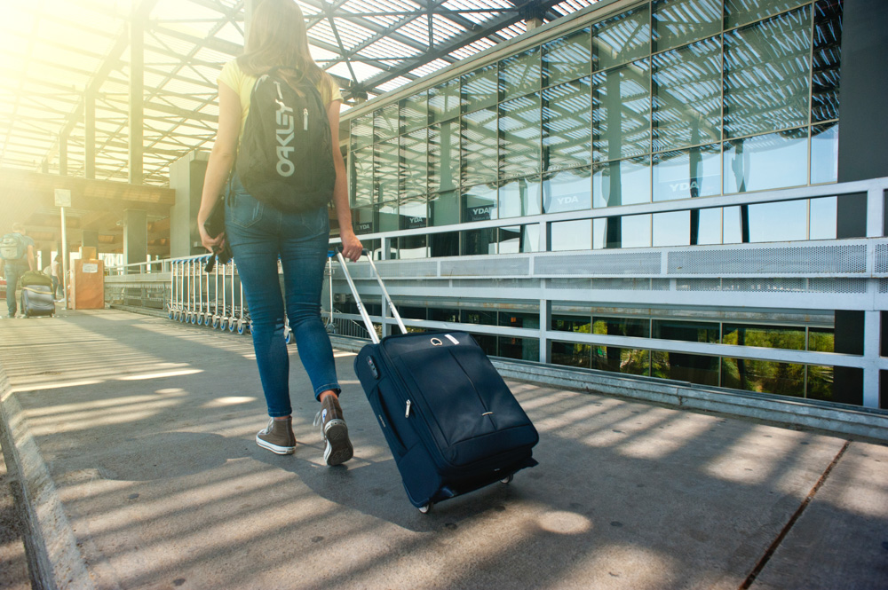 A woman with her suitcase - Smart travel packing tips