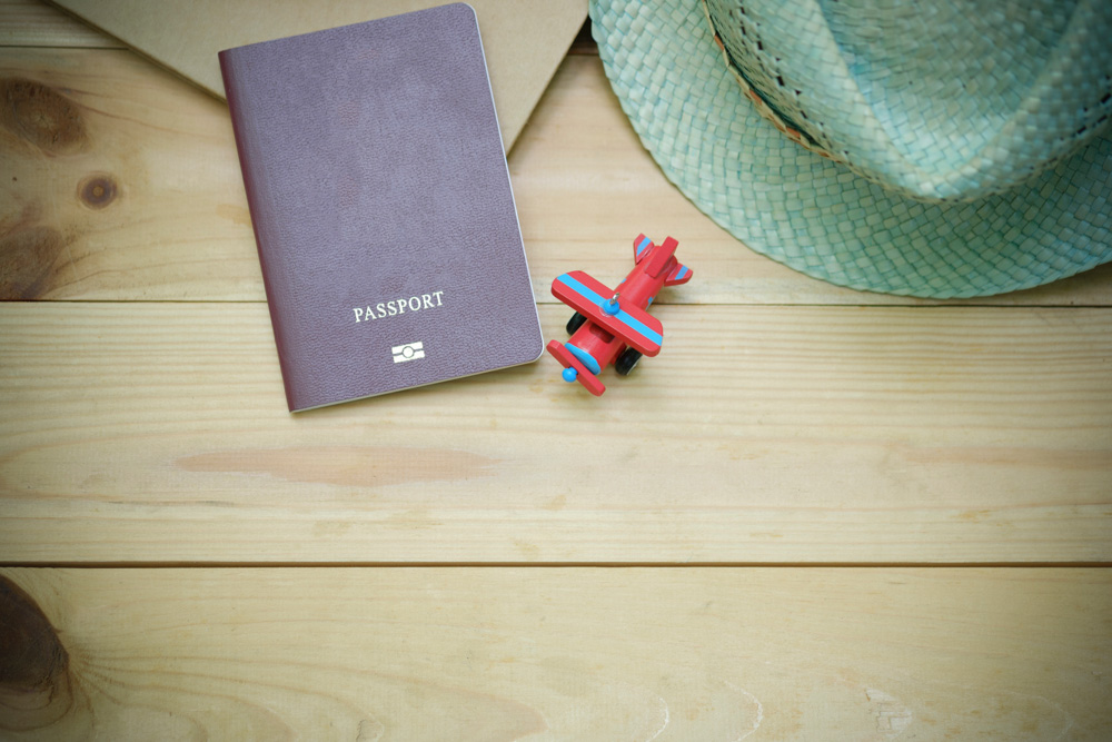 Passport on the table next to a hat