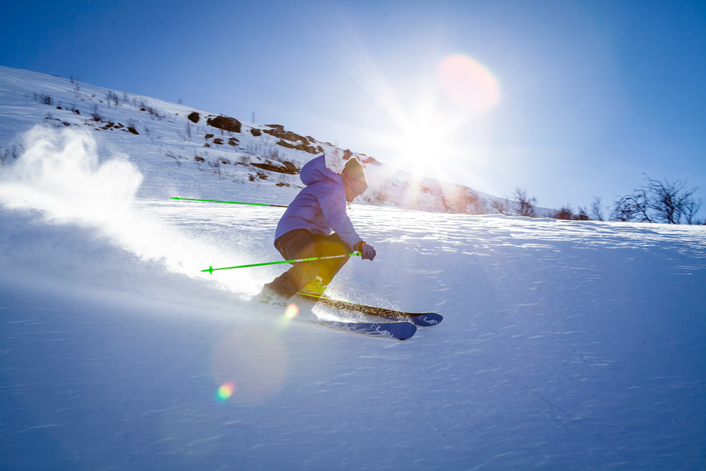 A man skiing fast down the mountain