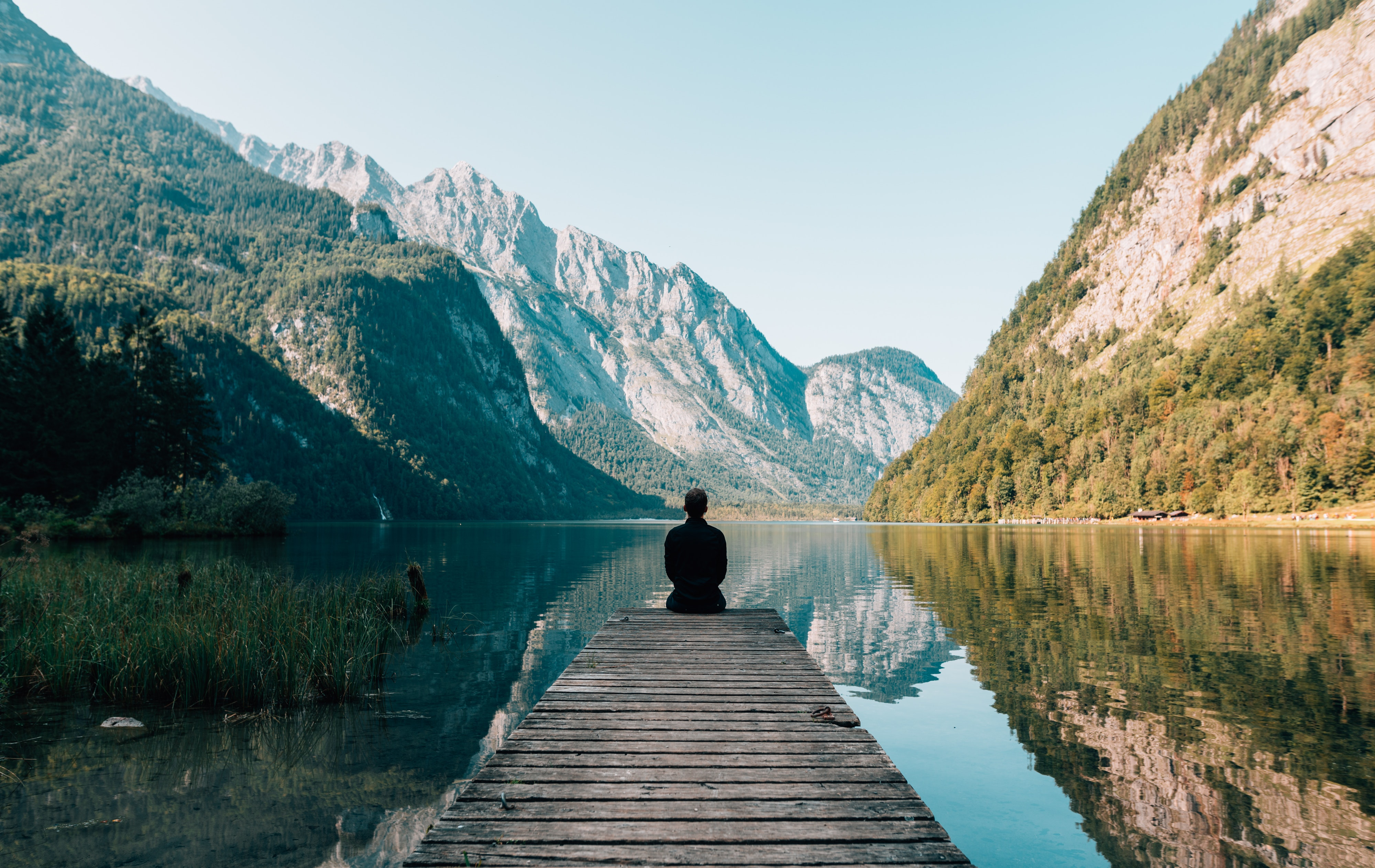 Person on a wooden bridge, surrounded by mountains