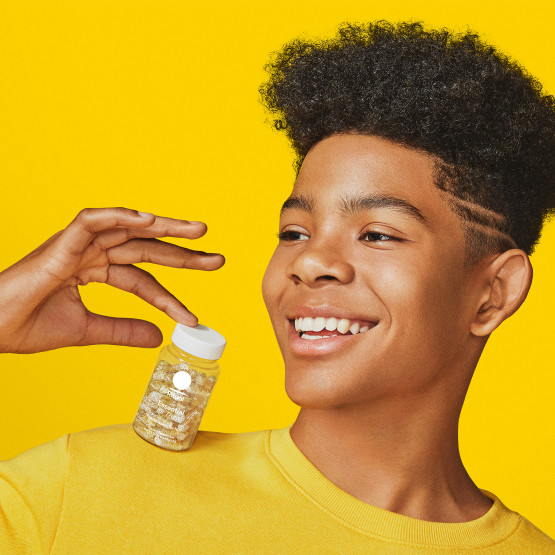 Teen boy model holding a bottle of Essential for Teens Multivitamin for Him