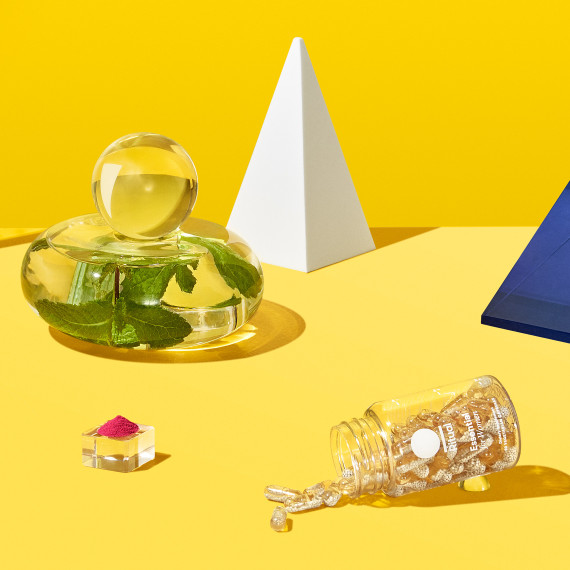 Ritual Essential for Women bottle shown in a yellow staged background with mint leaves and other props scatted around