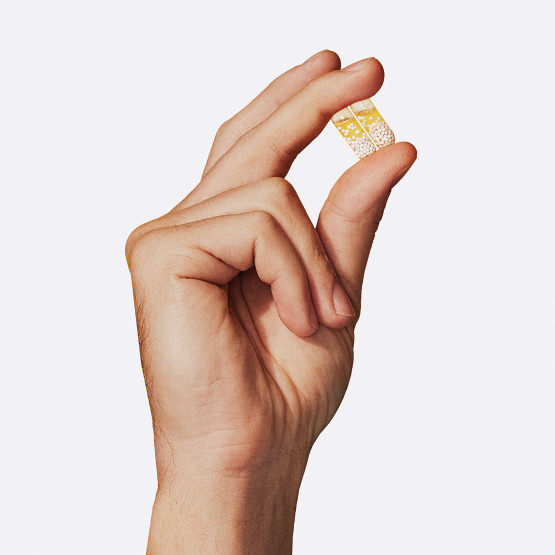 Closeup image of men holding 2 Essential for Men 18+ pills in hand