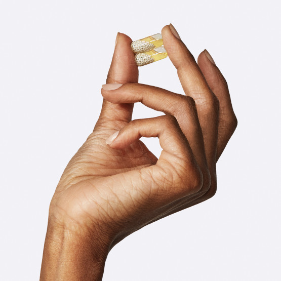 Closeup shot of woman holding 2 Ritual's Essential for Women 50+ pills in hand