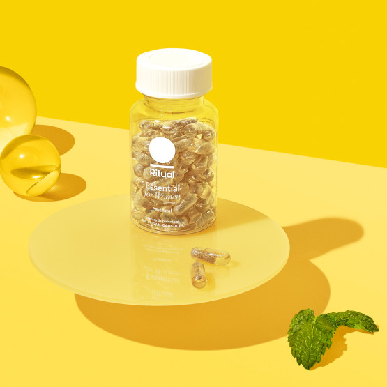 Ritual's Essential Postnatal bottle staged in yellow background with mint leave and clear capsules